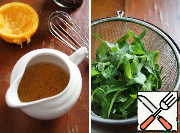 Wash and dry arugula.Prepare the dressing. Squeeze the orange juice, add oil, salt, pepper, mix with a whisk.