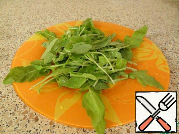 Put arugula on a flat salad plate in the middle.