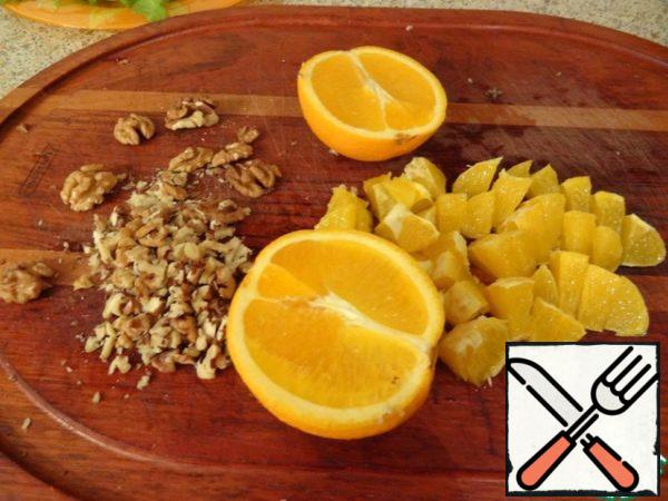 Walnut chop with a knife, wash oranges, clean and cut into slices.