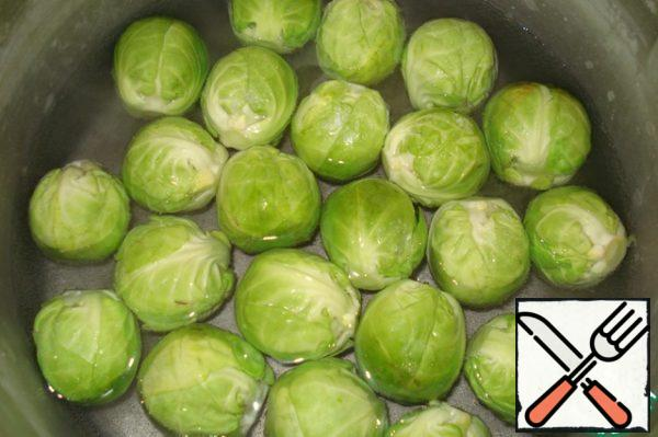 Boil Brussels sprouts in salted water. Sometimes cabbage is bitter, to avoid this trouble, I have there is secret. When the water boils, drain the water and pour a new one, add a few drops of lemon juice into the water with cabbage and boil for another 5-7 minutes.