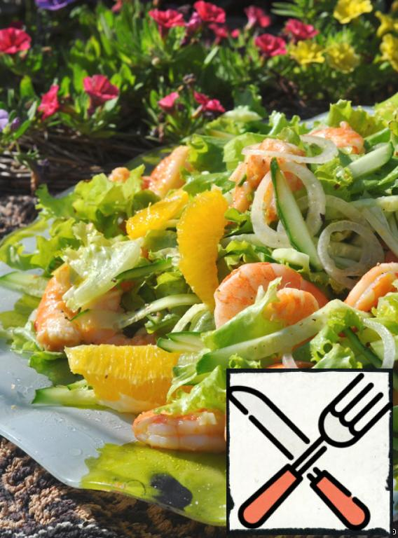 Add cucumber and shrimp to the lettuce and oranges. Freshen the salad with a few drops of oil on top.