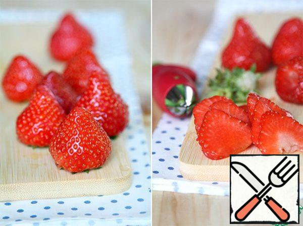 While cooking asparagus, take strawberries, wash, remove the tails, cut half of the thin plates, the second will send in a blender.
