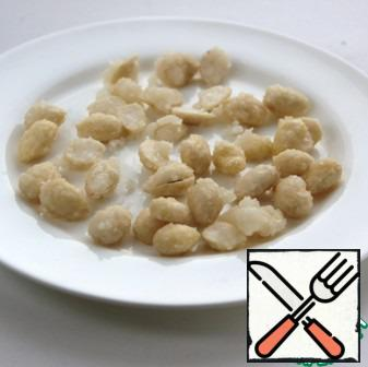 Put the almonds on a greased plate with vegetable oil, cool and chop.