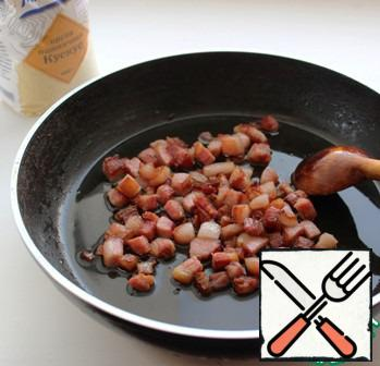 Heat 1 tbsp oil in a frying pan and fry the bacon in it until Golden brown. Bacon ready to pass on to the heated plate.