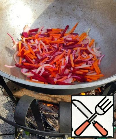 Remove the fat with a slotted spoon, add vegetables (onions, carrots, beets) to the cauldron. On high heat fry until Golden brown, stirring constantly. Remove vegetables with a slotted spoon into a clean bowl.