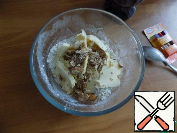 The butter should be spread from the fridge in advance so it is soft. Cut it into small pieces and spread to a mixture with nuts and two drops of almond flavor.