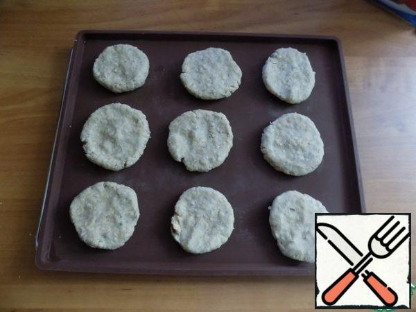 Prepare a baking sheet covered with baking paper. I'll use a silicone Mat. From the dough pieces tear off, roll into small balls, flattening them into cookies. Cookies turned 9 PCs D~ 5 cm and height-1 cm. Laid on the Mat with a distance from each other. The oven warmed up to t-180 C.