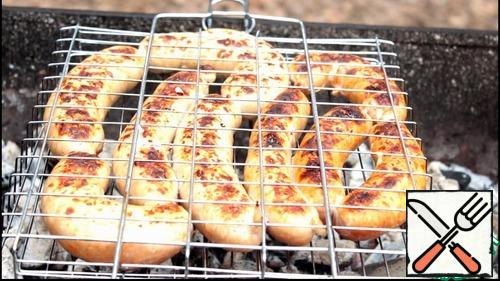 The grate is lubricated with vegetable oil, so the sausages do not stick to the grate. Spread not very tightly and fry on both sides until Golden brown. It took us about 5 to 10 minutes on each side. Sausages should be spread on the grill when the greatest heat passed and the coals were covered with white ash and acquired a whitish color. In this heat, they are perfectly prepared and not burn.