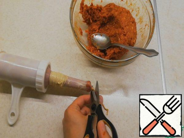 Rotating the handle of the piston, move the stuffing to the edge of the nozzle, so that initially there was no air inside the shell. Pull the part of the shell, sufficient to tie the knot, tie the knot, cut off the excess tail with scissors.