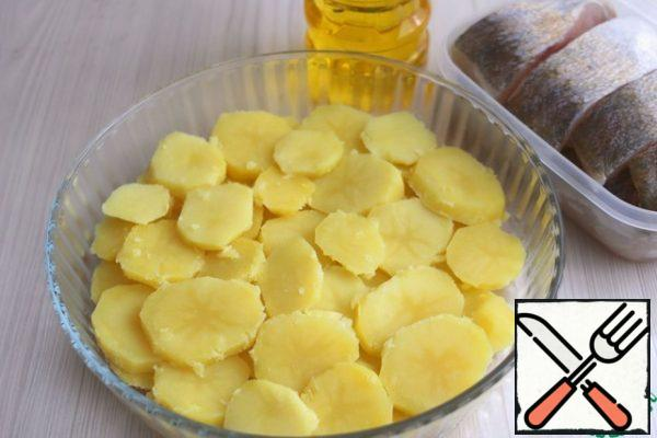 Boil potatoes (7 PCs.) to the state of Al dente in salted water, cool. Cut into plates 0.5 - 0.7 mm. At the bottom of the baking dish add 2 tablespoons of vegetable oil, put the plastic potatoes.