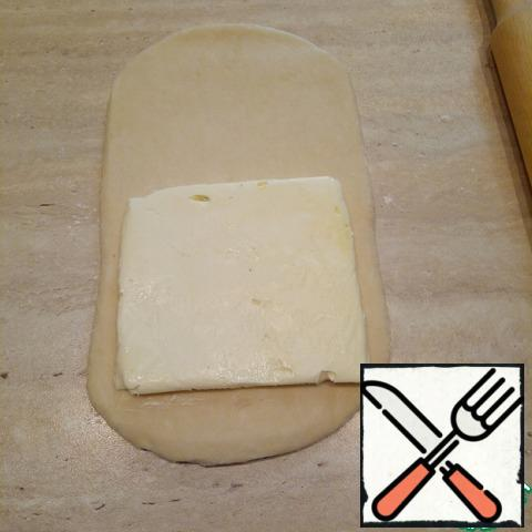 Now let's make puff pastry. After the allotted time to get the dough and butter from the refrigerator and leave on the table for 10 minutes, no more. Table pour flour, the dough on top too. To remove excess and roll out the dough into a rectangle 2 times more square of butter. Butter spread on the pastry and seal into a square.