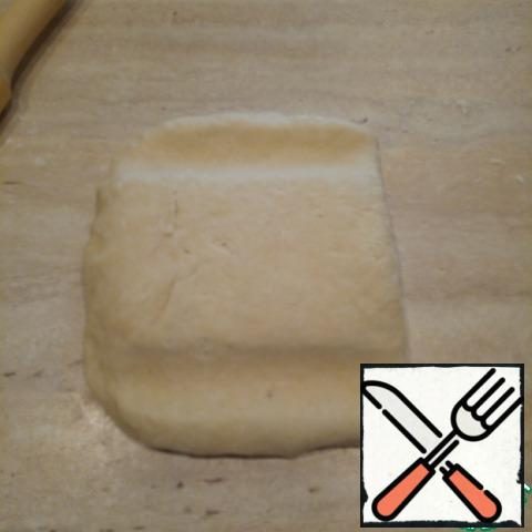 The edges of the pinch, on top of a little dust flour and place the dough fold on the right side. With a rolling pin to shove the top and bottom.