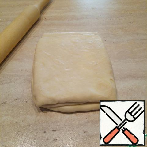 An hour later, the table to dust with flour, the dough to lay out the fold on the right (to dust with flour, remove excess) and roll out into a thin (0.5 cm thick) rectangle. The thickness of the must be same across the surface! Next, fold the dough three times - from themselves bend the edge of the dough and cover with another part. Walk a little rolling pin, a little flattened. In the photo, the dough after rolling, folded in 3. Again wrap in film and put in the refrigerator for another 1 hour.