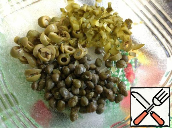 In a salad bowl put capers, pickled cucumbers to cut small cubes, olives slices.