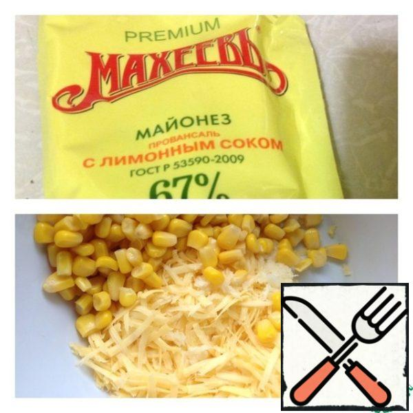 In a salad bowl put half a can of corn (drain excess liquid) and cheese, grated on a medium grater.