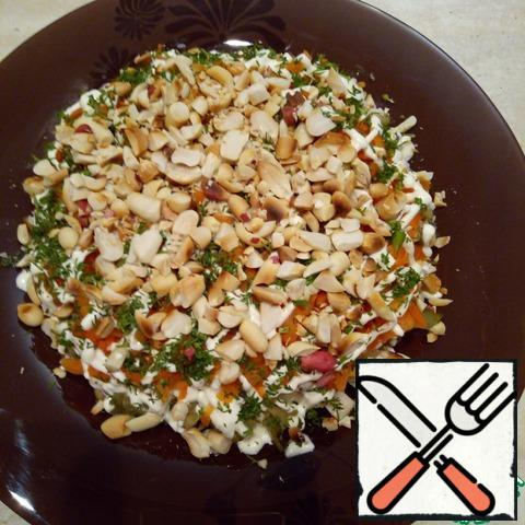 The fourth, the final layer - chopped dill and peanuts. Nuts are not worth much grinding! It is better to leave right halves, so much tastier! I went through the peanut, making a few movements of the knife.