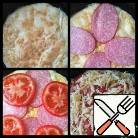 Once fried bottom, turn the spatula, put salami, tomatoes and sprinkle with grated cheese.