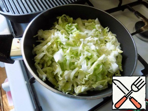 Make the filling for the cake. In a saucepan poured sunflower oil, warmed and put crushed garlic clove flat side of the knife. Fry it for a minute, until the garlic has given its flavor to the oil. Removed the garlic and laid out a large chopped onion. I used white onions. Can be take any. Onions gilded a couple of minutes and put the chopped young cabbage. Cabbage can be fried to your liking. I don't fry much. Cook the cabbage until soft. It's fast, 5 minutes. It's in the pie.