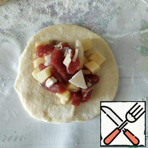 The dough is divided into small pieces. Roll out one piece and spread 1 tbsp filling, add 1/2 tsp butter.
