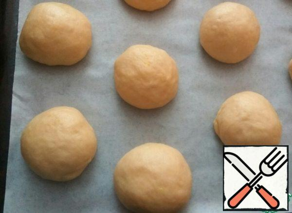 Punch down the risen dough and divide into 12 parts. Roll the balls. Put on a baking sheet covered with parchment at a distance from each other. Leave on for 15 minutes.