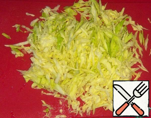 Chop the cabbage and grind with salt and pepper.