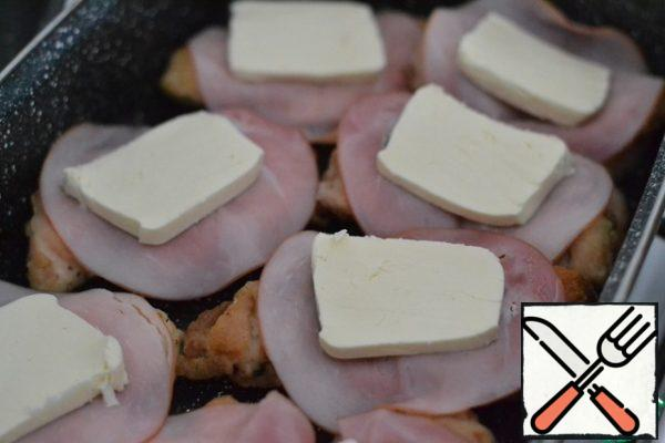 Put a piece of ham on each piece of breast. Put a plate of cheese on top.
