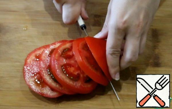 Wash the tomato and cut it into rings.