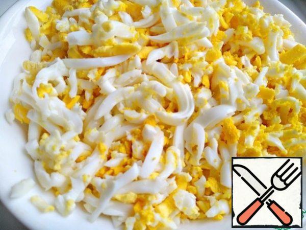 Eggs boil hard-boiled, peel, grate on a large grater.
