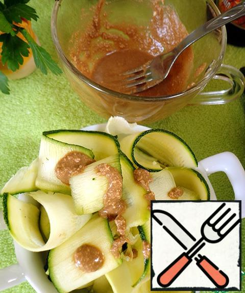 Zucchini folded into a salad bowl, pour the dressing.
