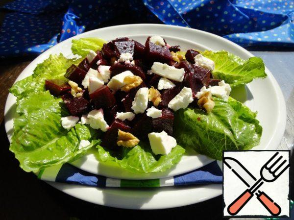 Spread the lettuce leaves on the dish and put the beets in the marinade on top. With your hands crumble the feta pieces. And we finish with walnuts. Pour the marinade.