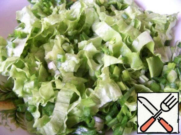 Cut the green onions and salad. Half of the onions mix with lettuce.