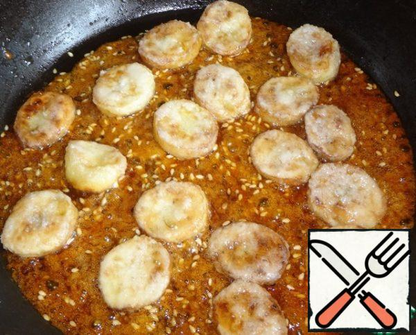 Put in caramel fried bananas and mix well. Sticks (or fork/spoon), which you will remove bananas from the pan, keep in cold water to caramel them not stuck. Take each piece and dip in water, and then put on a plate to solidify. Place the bananas on a plate and allow to cool.