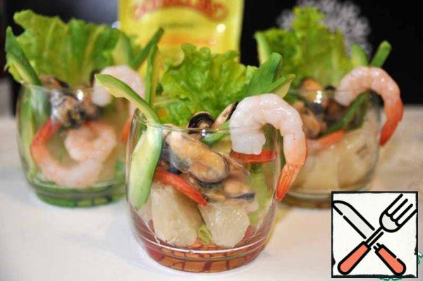 Randomly placed in a glass of pomelo, avocado, smoked mussels and shrimp.
