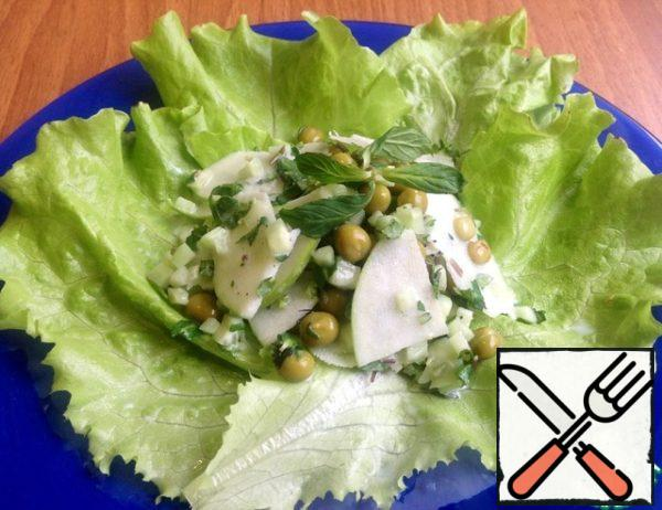 Lettuce put on a plate and then the salad itself, already seasoned with sauce and mixed.