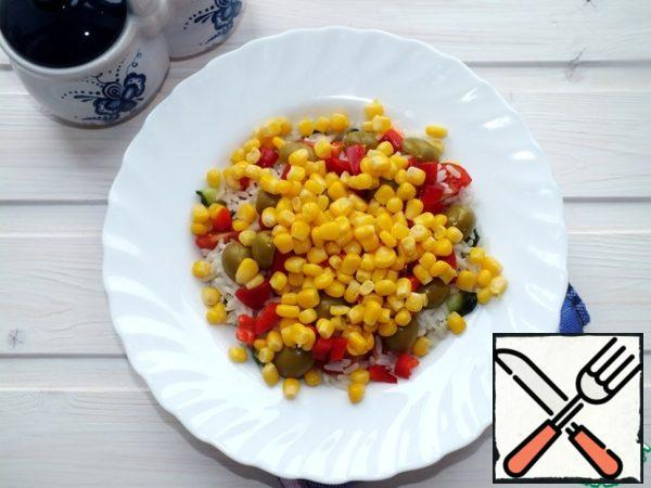 Spread the red pepper, cut into cubes and corn without liquid. Season with vegetable oil, salt, mix and spread in a salad bowl. Make out greens.