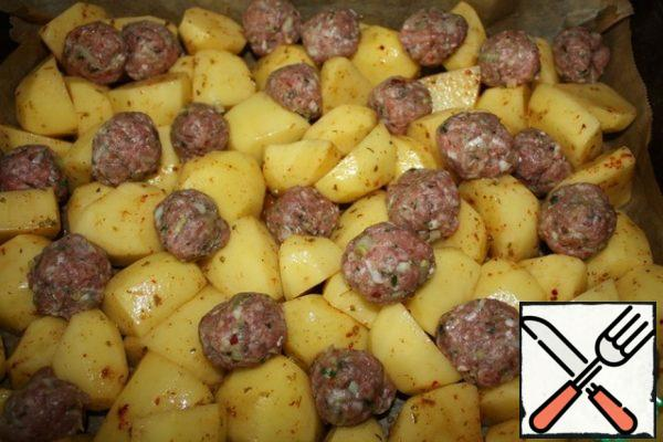 About the same size cut potatoes, salt and add your favorite spices to taste, add oil and mix well. Spread on a baking sheet mixed with meat balls. Add water. Preheat the oven and bake at a temperature of 200 degrees. about 40 minutes.