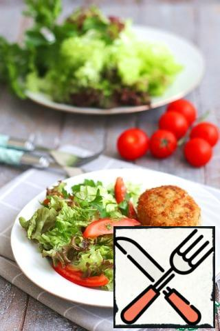 The cutlets garnish with a salad of fresh vegetables.