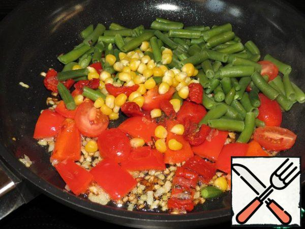 In a saucepan, heat the olive oil and fry in it until soft finely chopped onions, peppers, cherry, dried tomatoes, beans for 5 minutes over medium heat, stirring. Then add Basil, ground red pepper, salt and cook for another 5 minutes.