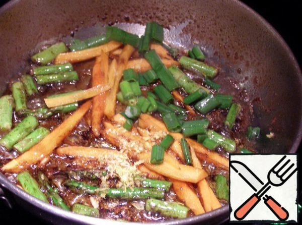 Asparagus cut, carrots finely cut into strips, ginger three and fry all the vegetable slicing in olive oil with soy sauce and 2 tablespoons of orange juice - 5 minutes, stirring constantly. Green onions cut and add at the end of frying for 1 minute.