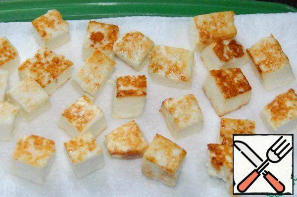 Cut the cheese into cubes, fry on both sides in vegetable oil in a strongly heated pan, to a beautiful rosy color. Spread on a napkin to stack the excess fat.