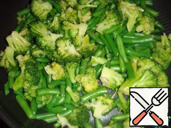 Broccoli disassemble into small inflorescences. Put together with string beans in a frying pan and pour a little water (if the vegetables are thawed, then they have enough liquid and water can not be added).