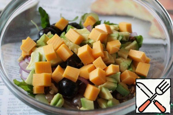 Peel the avocado, cut into cubes, sprinkle with lemon juice and add to the salad.