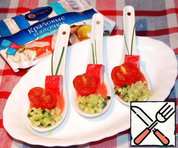 Now it is possible to serve: Pour tomato sauce on spoons, with edge to lay out cucumbers, to dip in sauce a piece of a crab stick, to decorate with feathers of green onions and the stewed tomato sprinkled with freshly ground pepper.