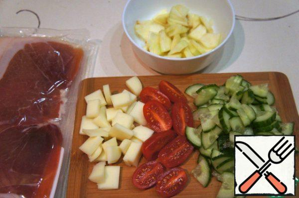 Cucumber and Apple cut into thin triangular slices, tomatoes cut in half, Suluguni cut into small cubes.