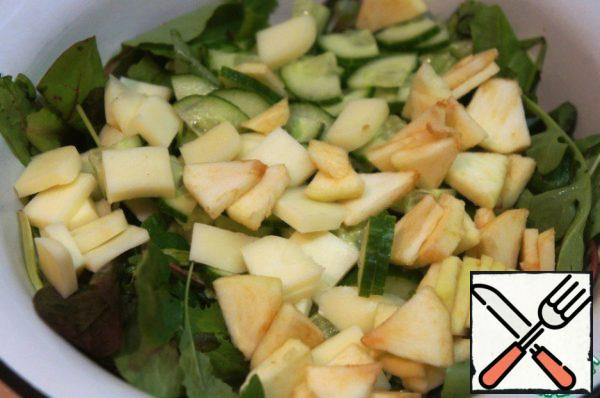 In a wide bowl pour the salad mix, add the cucumbers, cheese and Apple and mix gently.