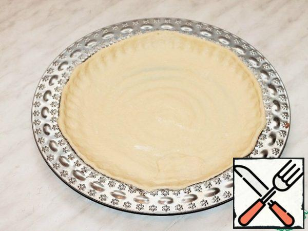 With a rolling pin, transfer the circle to a greased baking tray or baking dish (f=28 cm). Grease the dough with melted butter and sprinkle with starch (1 tsp).