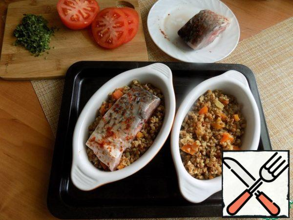 I'll serve the dish in portions. Smeared the molds with oil, put a layer of buckwheat on the bottom. From above-fish. On the fish put a slice of tomato. Top fish and tomatoes poured oil quite a bit, all beautifully cooked.