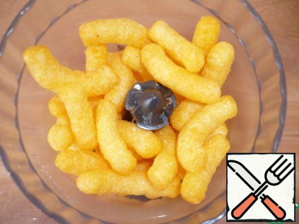 Pour the cheese-flavored corn sticks into a food processor and chop.
