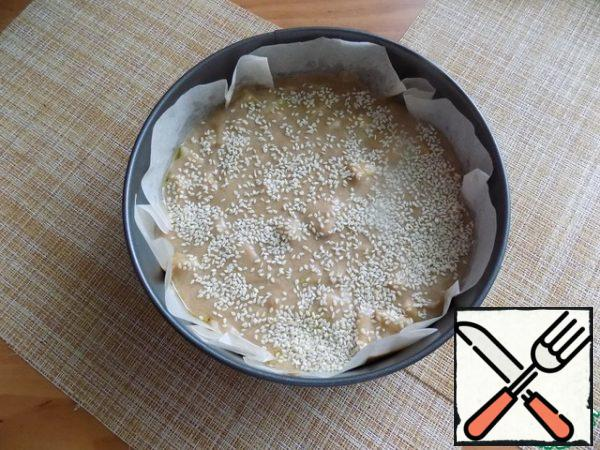 Warm the oven to t-180 C. for baking, I will use a split ring D-20 cm. I will Lay it with baking paper. The paper is not oiled and I smeared it with a little oil. Put the dough and evenly distributed. On top sprinkle generously with sesame seeds white. You can sprinkle with seeds or chopped nuts. Put in the oven, setting the time 30 minutes.