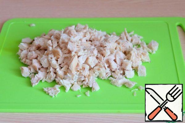 Boil chicken fillet in salted water, then cut into small cubes.